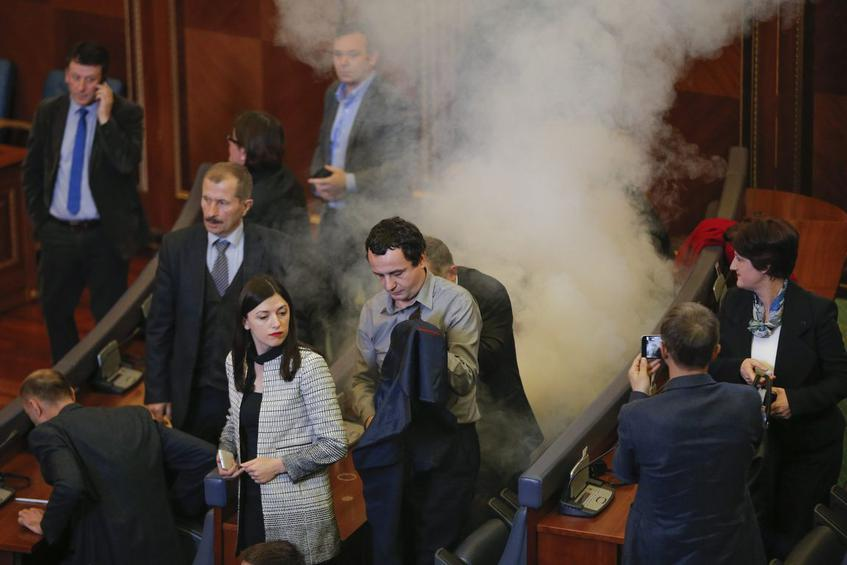 Opposition lawmakers throw tear gas during a plenary session at Kosovo's parliament