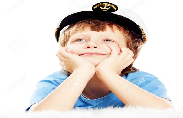 9467834-Cute-tr-umend-Kind-in-Captain-Cap-liegt-an-der-weiche-Schafe-Pelz-isolated-over-white-Background-Hoh-Lizenzfreie-Bilder